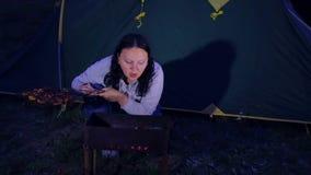 Una donna ad una tenda e ad un fuoco arrostisce la carne e gonfia i carboni video d archivio