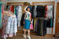 Una donna alla moda che sta su un fondo dei vestiti Una ragazza con un sacchetto della spesa che prova su un cappello blu alla mo fotografia stock libera da diritti