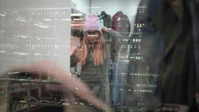 Una donna alla moda dei pantaloni a vita bassa che prova sui vestiti alla moda nel deposito Vista attraverso la finestra Acquisto archivi video