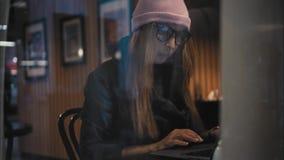 Una donna alla moda dei pantaloni a vita bassa si siede in un caffè per una tavola, apre il computer portatile e comincia lavorar stock footage