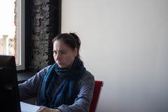Una donna alla tavola che lavora al computer fotografia stock libera da diritti