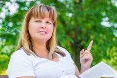 Una donna allegra di 50 anni sul banco Fotografie Stock