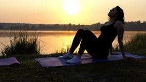 Una donna allegra si siede ed alza il suo stomaco su una stuoia alla Banca del lago archivi video