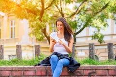 Una donna allegra in un parco facendo uso del suo Smartphone immagine stock