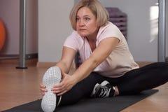 Una donna anziana è impegnata nell'allungamento alla palestra immagini stock