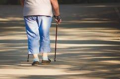 Una donna anziana è impegnata nella passeggiata scandinava nel parco, Russia immagine stock