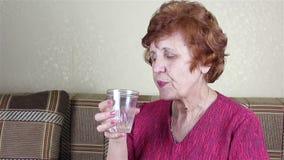 Una donna anziana beve l'acqua da un vetro video d archivio