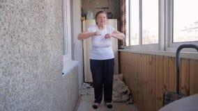 Una donna anziana anziana che fa gli esercizi di mattina stock footage