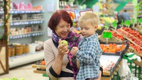 Una donna anziana con il suo piccolo nipote comprare le mele fresche in grande supermercato archivi video