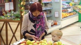 Una donna anziana con il suo piccolo nipote comprare le mele fresche in un supermercato stock footage