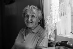 Una donna anziana emozionale dice nella sua casa felice Fotografia Stock Libera da Diritti