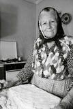 Una donna anziana felice e sorridente, la nonna, anziano è cuocere, cucinante nella cucina a casa accogliente Cultura europea med immagini stock