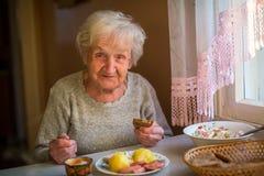 Una donna anziana felice mangia a casa Fotografia Stock Libera da Diritti
