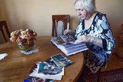 Una donna anziana guarda attraverso un album di foto fotografia stock libera da diritti