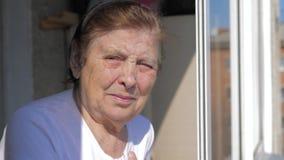 Una donna anziana guarda dalla finestra video d archivio