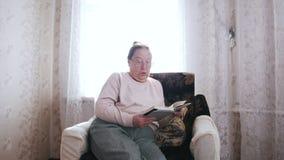 Una donna anziana ha camminato per presiedere, sedersi ed aprire un libro sui precedenti della finestra archivi video