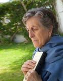 Una donna anziana ha messo il libro vicino al suo cuore Immagine Stock Libera da Diritti