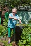 Una donna anziana nel giardino con acqua Fotografia Stock Libera da Diritti