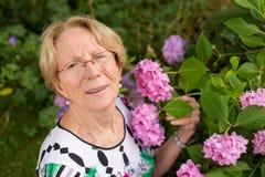 Una donna anziana piacevole sta posando davanti ai bei fiori rosa Fotografie Stock Libere da Diritti