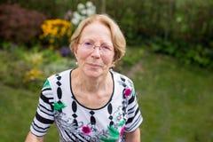 Una donna anziana piacevole sta sognando in bello GA Immagine Stock