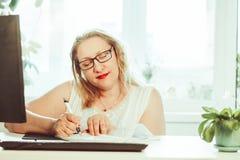 Una donna anziana scrive con una penna immagine stock