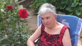 Una donna anziana si siede in una sedia sulla natura stock footage