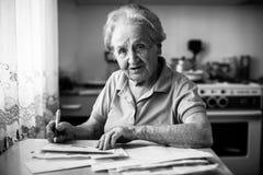 Una donna anziana soddisfa le condizioni per il pagamento delle infrastrutture collettive aiuto fotografia stock