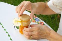 Una donna anziana sta aprendo un vetro di marmellata d'arance Immagini Stock Libere da Diritti