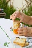 Una donna anziana sta aprendo un vetro di marmellata d'arance Immagini Stock