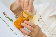 Una donna anziana sta aprendo un vetro di marmellata d'arance Fotografia Stock