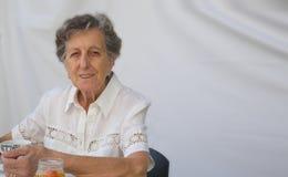 Una donna anziana sta avendo sua prima colazione Immagine Stock Libera da Diritti