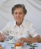 Una donna anziana sta avendo sua prima colazione Fotografie Stock Libere da Diritti