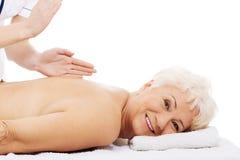 Una donna anziana sta avendo un massaggio. Concetto della stazione termale. immagini stock libere da diritti