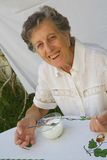 Una donna anziana sta mangiando un yogurt casalingo Fotografia Stock Libera da Diritti