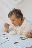 Una donna anziana sta mangiando un yogurt naturale casalingo Fotografie Stock Libere da Diritti