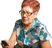 Una donna anziana sta rivolgendo ad un telefono cellulare, isolato. fotografie stock