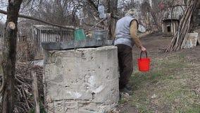 Una donna anziana in un villaggio abbandonato sta riunendo l'acqua da un pozzo in un secchio, vivente da solo archivi video