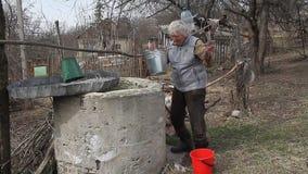Una donna anziana in un villaggio abbandonato sta riunendo l'acqua da un pozzo in un secchio, vivente da solo stock footage