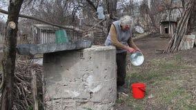 Una donna anziana in un villaggio abbandonato sta riunendo l'acqua da un pozzo in un secchio, vivente da solo video d archivio