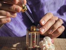 Una donna apre l'olio del profumo Olio profumato in polsi del ` s delle donne Olio arabo del profumo immagine stock libera da diritti