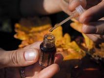 Una donna apre l'olio del profumo Olio profumato in polsi del ` s delle donne Olio arabo del profumo immagine stock