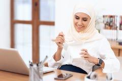 Una donna araba in un hijab sta pranzando immagine stock