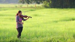 Una donna asiatica che gioca violino sul campo di erba archivi video