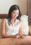 Una donna asiatica che per mezzo del dispositivo mobile Immagine Stock
