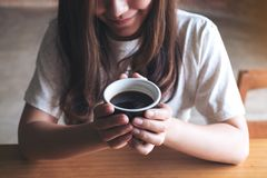 Una donna asiatica che tiene una tazza di caffè prima del bere con sentiresi bene in caffè Fotografia Stock Libera da Diritti