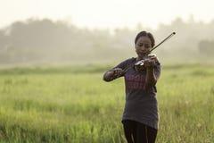 Una donna asiatica sta giocando il violino sul giacimento del riso Fotografia Stock