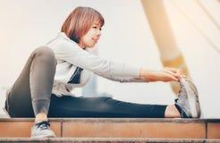 Una donna asiatica sta riscaldandosi per esercitarsi in una grande città guar fotografie stock libere da diritti