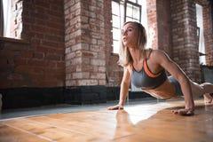 Una donna atletica che si scalda sull'addestramento Esercitarsi per la parte posteriore e la spina dorsale immagini stock libere da diritti