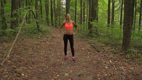 Una donna atletica funziona lungo Forest Track, si ferma Poiché ` m. stanco e riposare di I archivi video