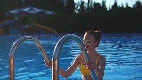 Una donna attraente con una buona figura emerge da una piscina all'aperto archivi video